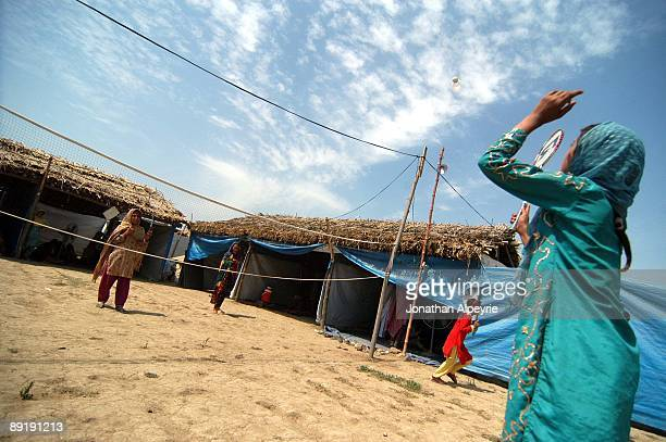 Two Pashtun refugee girls are playing Bagmington in the play yard near the makeshift classroom June 24 in Pakistan