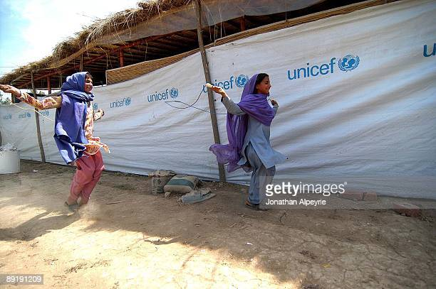 Two Pashtun refugee girls are playing with their cords in the play yard near the makeshift classroom June 24 in Pakistan