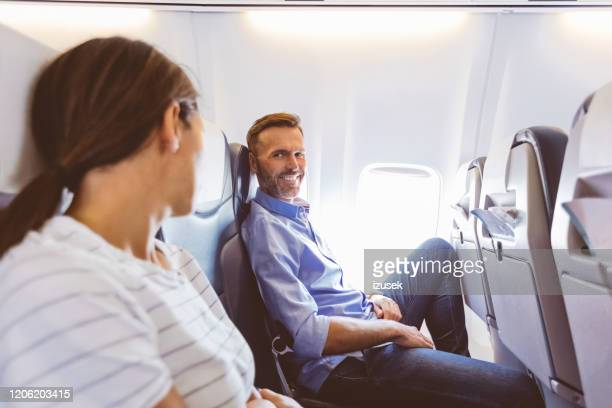 two passenger talking in the airplane - beautiful people stock pictures, royalty-free photos & images