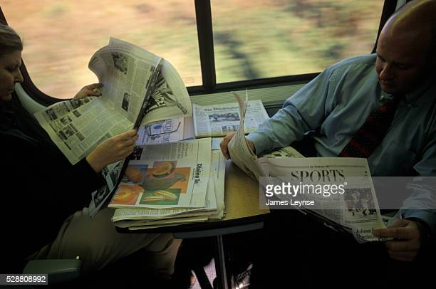 Two passengers aboard Amtrak's Acela Express read newspapers The high speed train which reaches speeds of up to 150 miles per hour travels between...