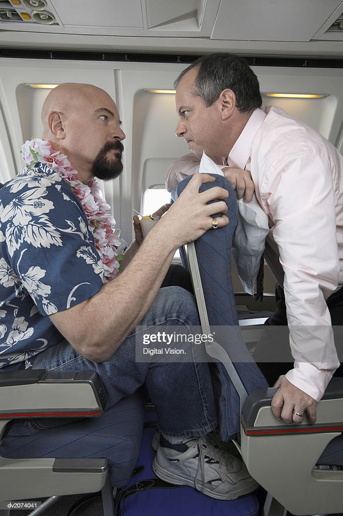 Two Passengers Looking Eye to Eye on an Aeroplane Angry About Seating Space : Stock Photo