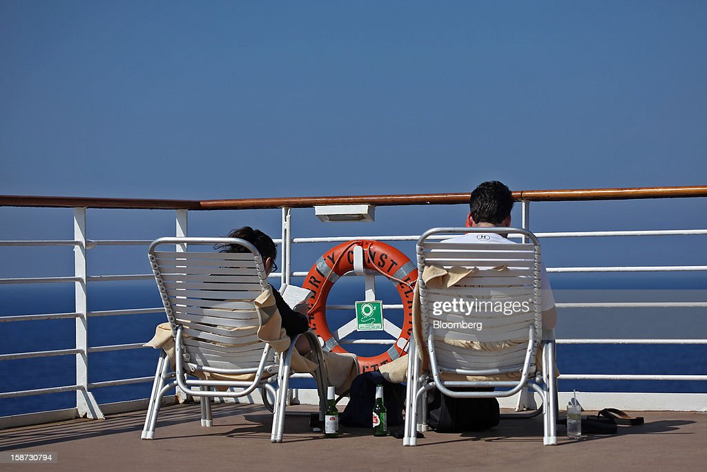 Two passengers read on lounge chairs aboard Celebrity Cruises Inc.'s Constellation cruise ship in the Caribbean Sea near the coast of Cuba on Wednesday, Dec. 19, 2012. Royal Caribbean Cruises Ltd. operates Azamara Club Cruises, Celebrity Cruises, CDF Croisieres de France, Pullmantur Cruises and Royal Caribbean International. Photographer: Tim Boyle/Bloomberg via Getty Images