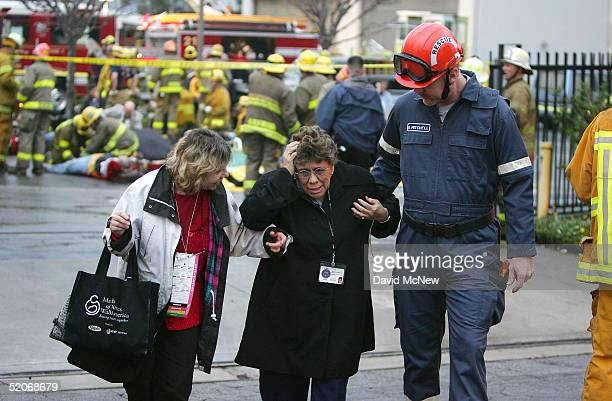Two passengers that were in a commuter train wreck are led away from the triage area January 26 2005 in Glendale California The twotrain wreck...