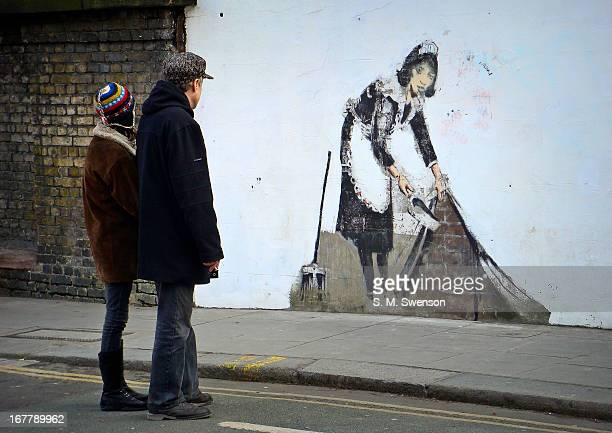 Two passers-by stop to take in Banksy's street art piece, 'Maid in London'. This is in Chalk Farm, North London. It is an overcast winter's afternoon...