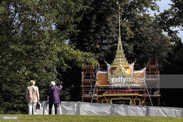 Two passers-by watch a Thai pavillion being constructed 12 September 2007 in Lausanne. Thailand is building a typical pavillion decorated with gold...