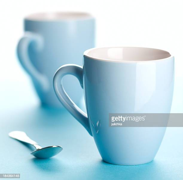Two pastel blue coffee cups and a spoon on blue table