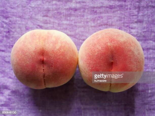 Two peaches on purple linen cloth