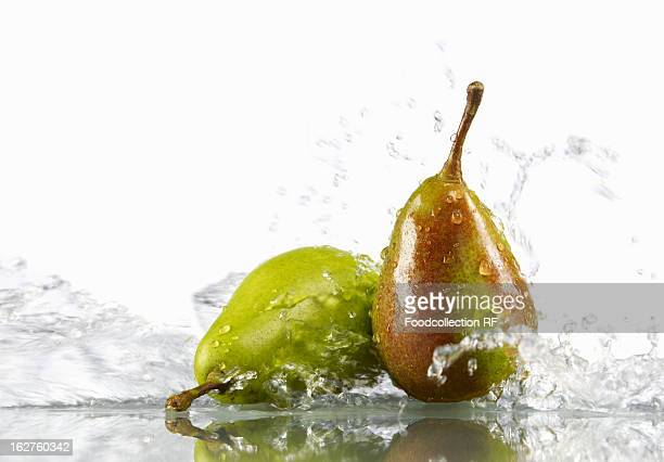Two pears splashing in water against white background