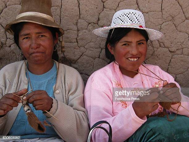 Two peasant women knitting in the prairie. Indigenous women from Juliaca in the Peruvian altiplano, use to meet to weave traditional products to...