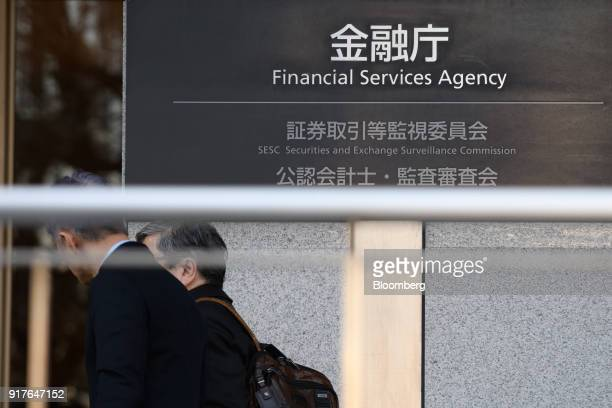 Two pedestrains walk past the Financial Services Agency headquarters in Tokyo Japan on Tuesday Feb 13 2018 Cryptocurrency exchange Coincheck inc...