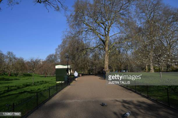 Two pedestrians observe social distancing as they walk in Green Park in central London on March 24 2020 after Britain ordered a lockdown to slow the...