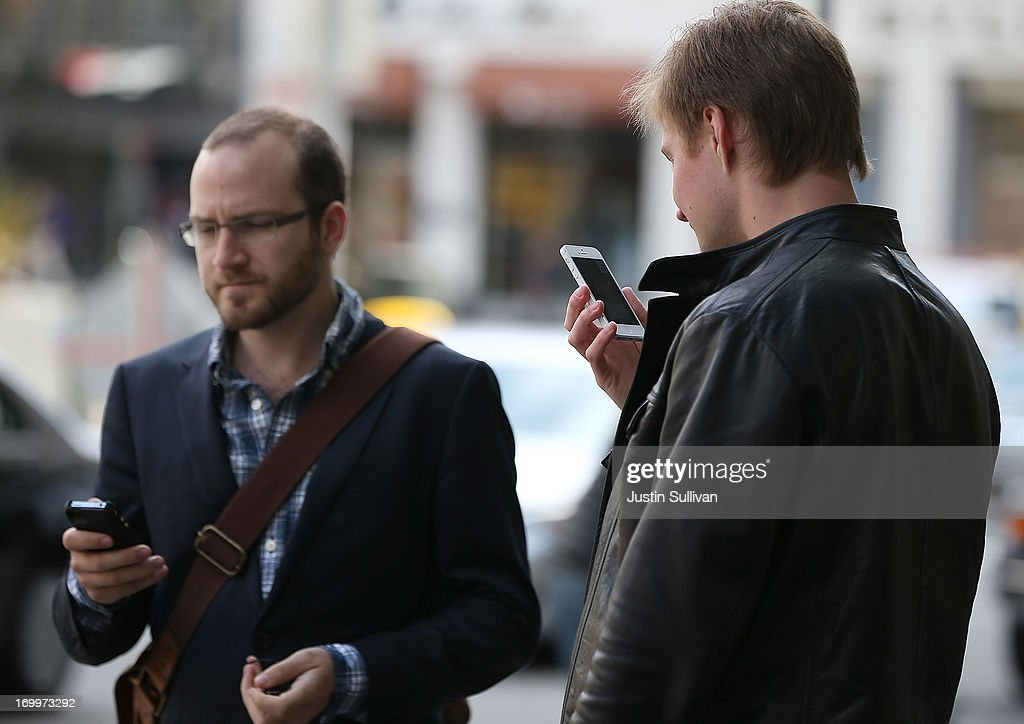 Two pedestrians use iPhones as they walk in Union Square on June 5, 2013 in San Francisco, California. According to a study by the Pew Internet & American Life Project, over half of American adults, or 56 percent, have smartphones, up from 35 percent two years ago.