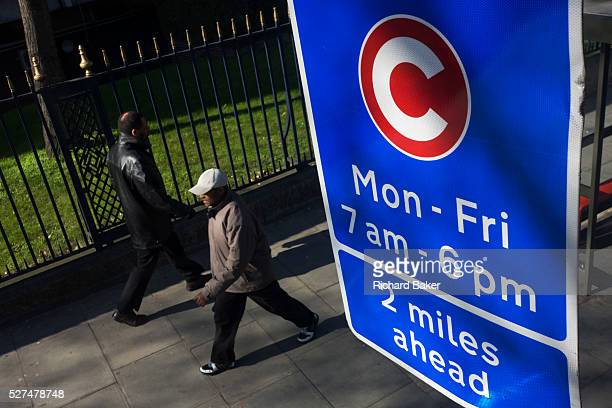 Two pedestrians walk beneath a motorists' Congestion Zone sign on a London street Seen from the top deck of a bus we see from an aerial perspective...