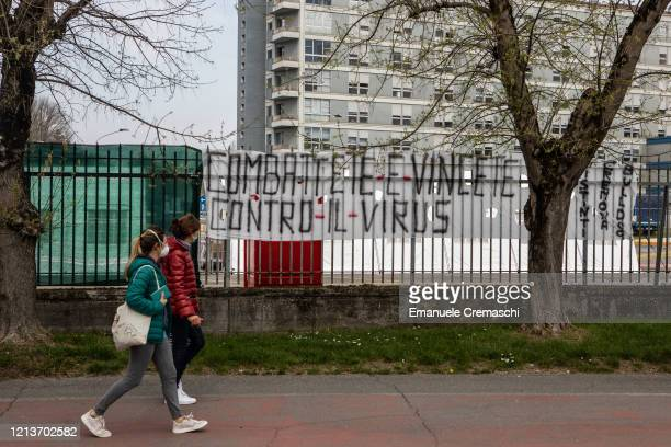 Two pedestrians walk past a banner that reads 'Fight and win against the virus' in front of Cremona Hospital on March 20 2020 in Cremona near Milan...