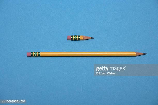 Two pencils, new and short one, against blue background