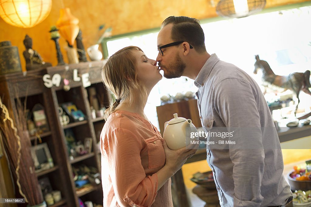 Two people, a couple running an antique store. Small business. Kissing each other.  : Stock Photo