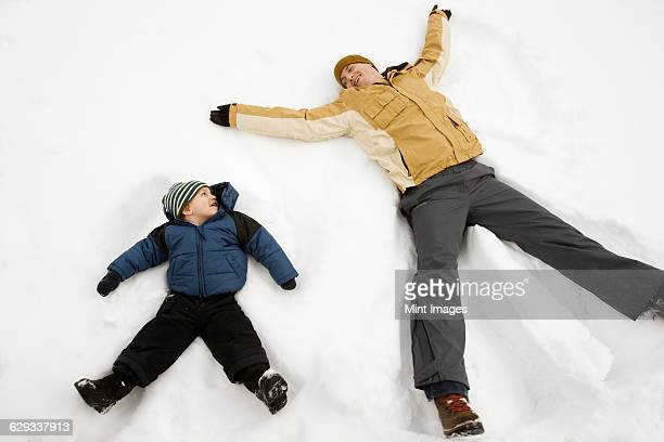 Two people, a man and a child lying in the snow make snow angel shapes.