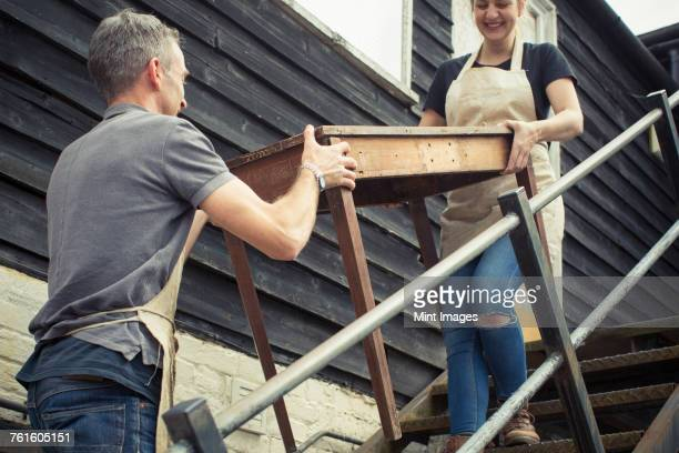 two people, a man and a young woman carrying an antique wooden table up steps. - portare foto e immagini stock