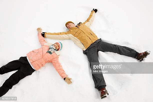two people, a man and woman lying in the snow make snow angel shapes.  - snow angel stock photos and pictures