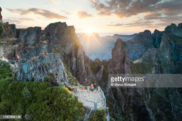 two people admiring sunset from pico do arieiro. madeira island, portugal - mountain range stock pictures, royalty-free photos & images