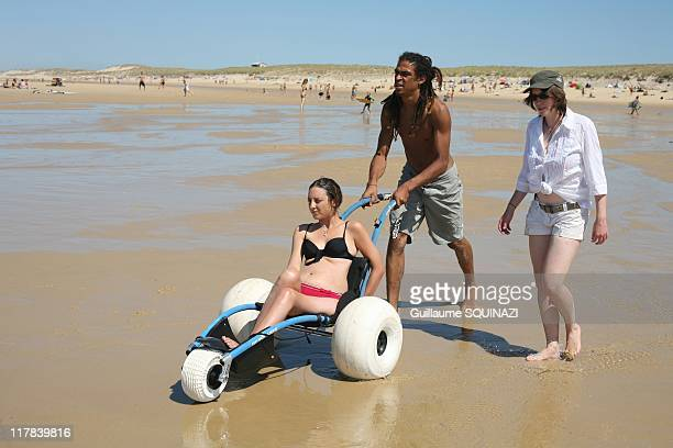Two people are needed to help a member of the French Association Vagdespoir get in the water and three to help them surf on August 23 2009 in Lacanau...