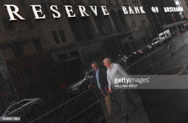 Two people are reflected in the wall as they walk past the Reserve Bank of Australia in Sydney on March 7 2017 Australia's central bank left interest...