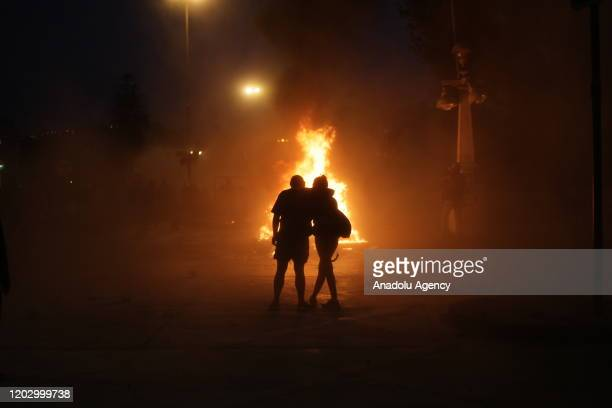 Two people are seen behind a fire during a protest against government at Vina del Mar Music Festival's opening in Vina del Mar, Chile on February 23,...
