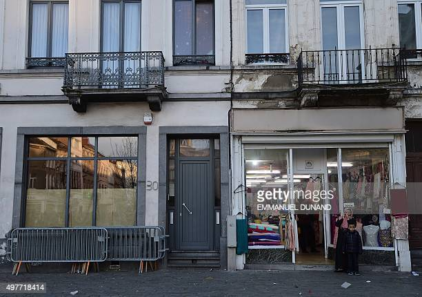 Two people are seen outside the Abdeslam family's apartment in Brussels' Molenbeek district close to the Town's Square where a vigil was earlier held...