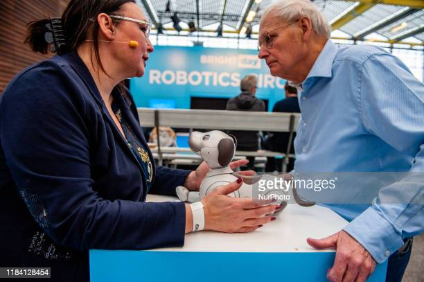Two people are talking while in the middle is Aibo robot of Sony during the Bright Day Festival in Amsterdam on November 23rd 2019