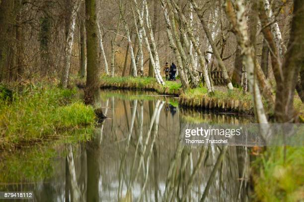 Two people are walking along a canal of the Spree in the Spreewald Biosphere Reserve on November 20 2017 in Luebbenau Germany