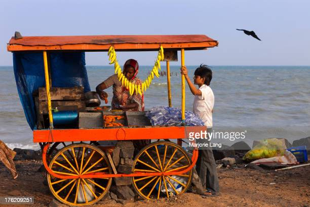 Two people at a food stall with snacks by the sea shore in Puducherry , an Indian Union territory enclave in Tamil Nadu, India.