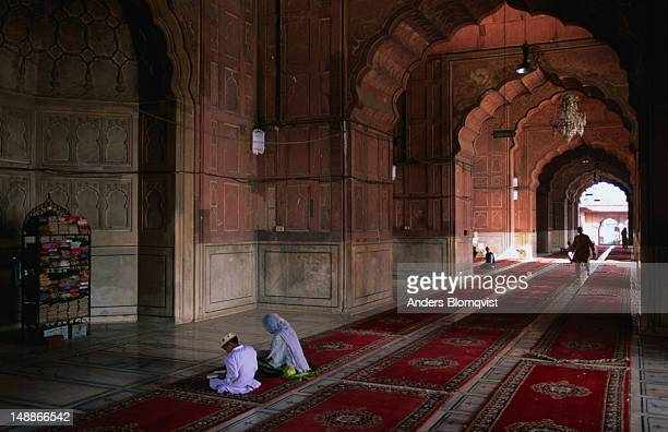 Two people at prayer on carpets in the main prayer room of the Jama Masjid in Old Delhi, India's largest mosque, built in the seventeenth century.