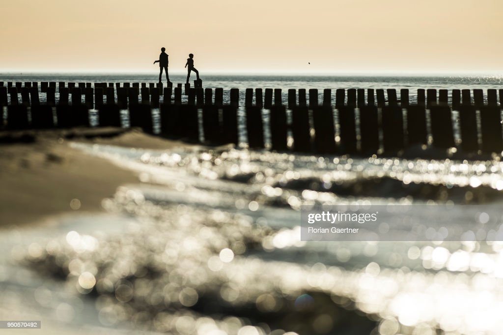 Two people balance on groynes at the Baltic Sea on April 21, 2018 in Warnemuende, Germany.