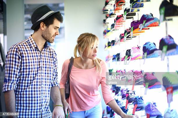 Two people buying shoes in retail store.