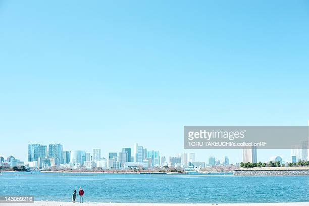 Two People by Tokyo Bay, Odaiba Skyline in Background