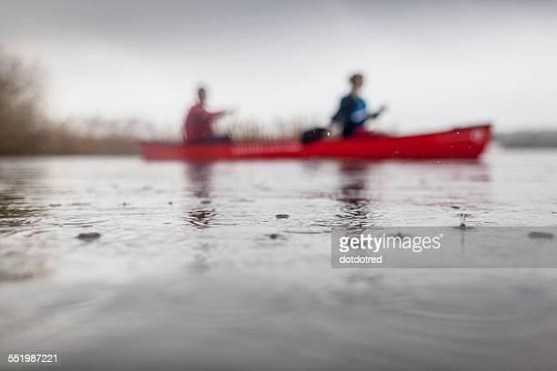 Two people canoeing in rain