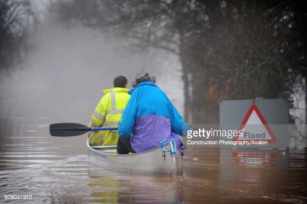 Two people canoeing past flood sign during floods Gloucestershire UK 2007
