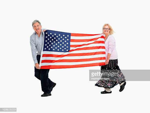 Two people carrying the American flag