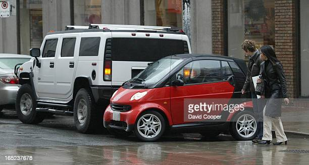 Two people check out the Smart car on Yonge at Shutter parked behind one of the bigger vehicles on the streets of Toronto a Hummer Smart cars are so...
