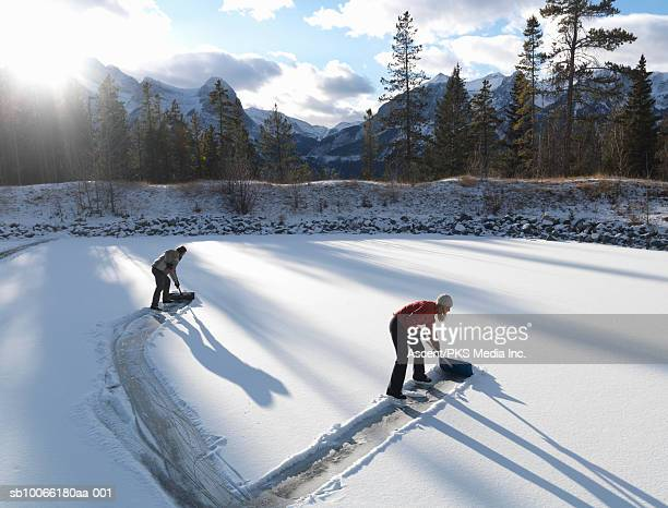 two people clearing skating rink with shovels - ice rink stock pictures, royalty-free photos & images