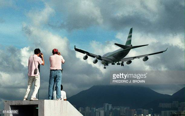 Two people climb onto a rooftop in Kowloon City 13 June to photograph an aircraft approaching Hong Kong's soontoclose Kai Tak airport runway The...