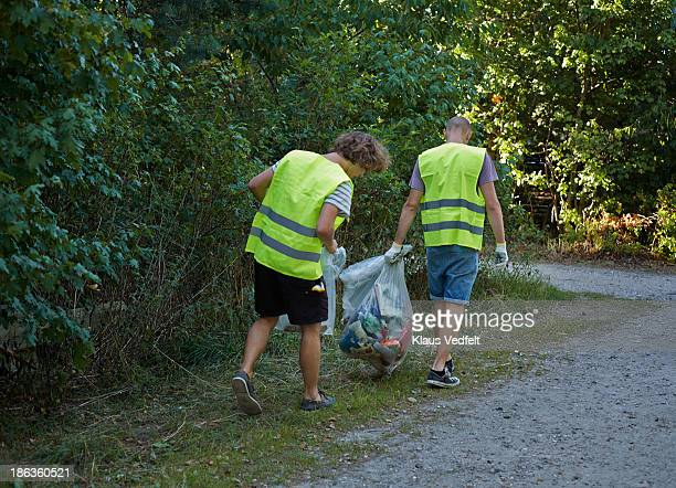 Two people collecting trash in the nature