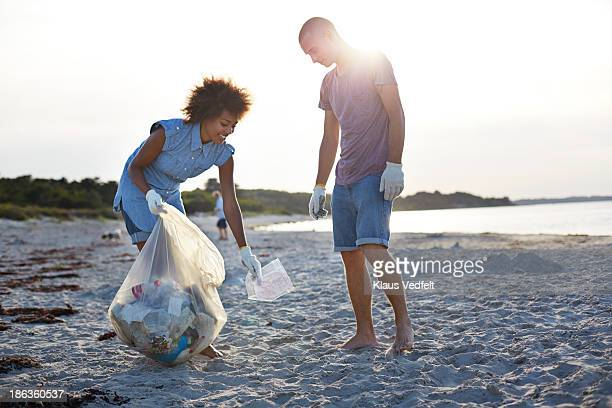 two people collecting trash on beach - sollevare foto e immagini stock