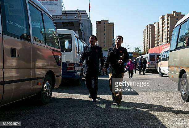 Two people coming from North Korea walk in the parking lot of Dandong Customs China handles roughly 40% of North Korea's worldwide export trade and...