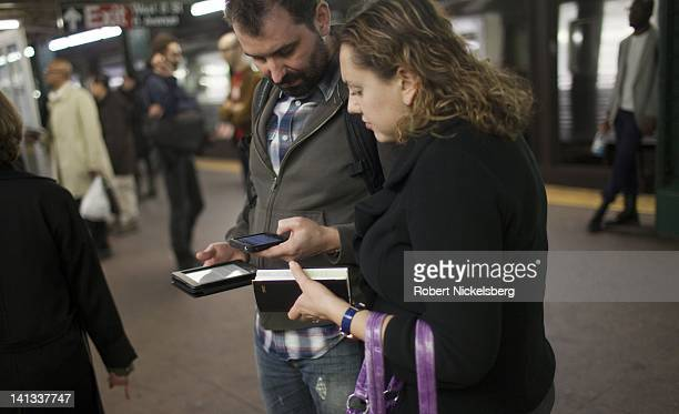 Two people coordinate their information using a variety of handheld electronic devices March 12 2012 while waiting for a subway in New York City