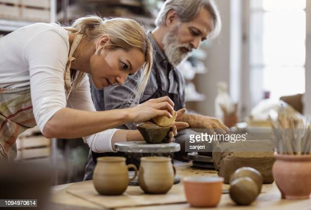 two people creating pottery - hobbies stock pictures, royalty-free photos & images