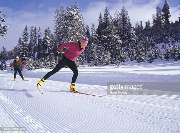 two people cross-country skiing - nordic skiing event stock pictures, royalty-free photos & images