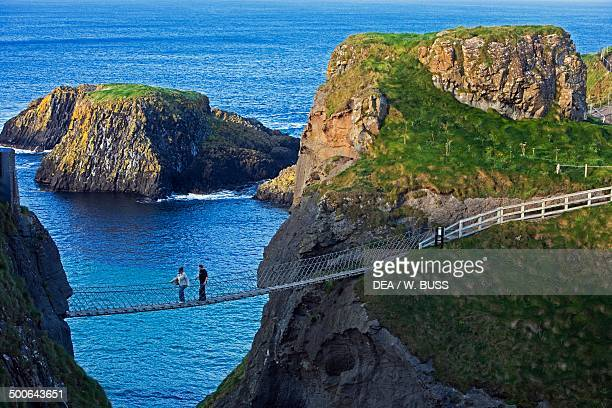 Two people crossing the rope bridge at CarrickaRede near Ballintoy Northern Ireland United Kingdom