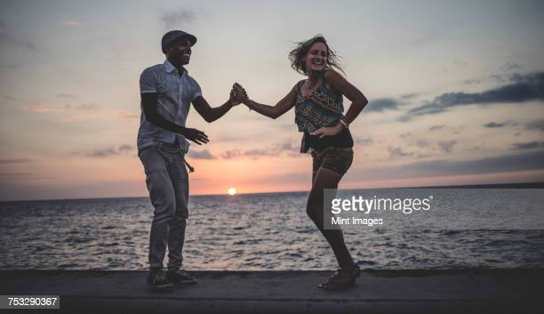 Two people dancing on a sea wall in front of the ocean at dusk.