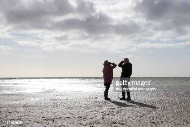 two people do an elbow pump on sandy beach - elbow bump stock pictures, royalty-free photos & images